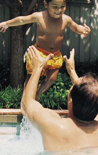 Father Catching his Son Diving into a Swimming Pool : Stock Photo