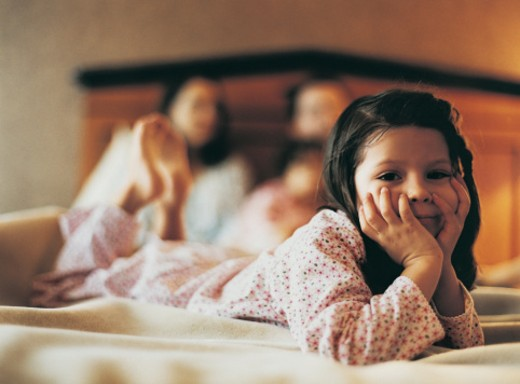 Portrait of a Girl in Bed with her Parents in the Background : Stock Photo