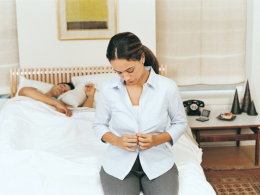 Woman Sitting on a Bed getting Dressed, Man Sleeping : Stock Photo