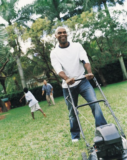 Man Mowing the Lawn, Boy and Senior Man in the Background : Stock Photo
