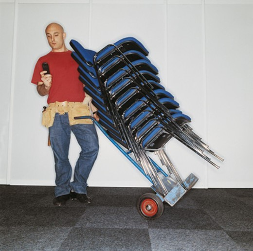 Workman Using a Mobile Phone and Holding a Hand Truck Loaded With a Stack of Chairs for a Business Conference : Stock Photo