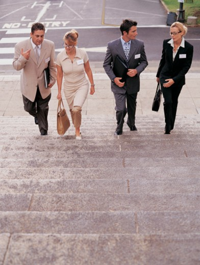 Four Business Executives Walking Up Steps in a City : Stock Photo