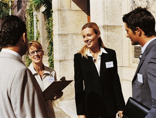Two Businesswomen Greeting Businessmen Outside a Building's Entrance : Stock Photo