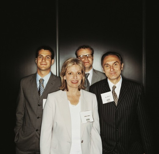 Stock Photo: 1527R-605068 Portrait of a Group of Four Business Executives Standing by a Wall