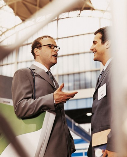 Two Businessmen Standing Face to Face in Discussion at a Business Conference : Stock Photo