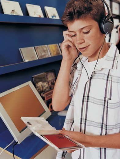 Stock Photo: 1527R-606005 Young Boy Listening to a Music Cd in a Record Shop on Headphones
