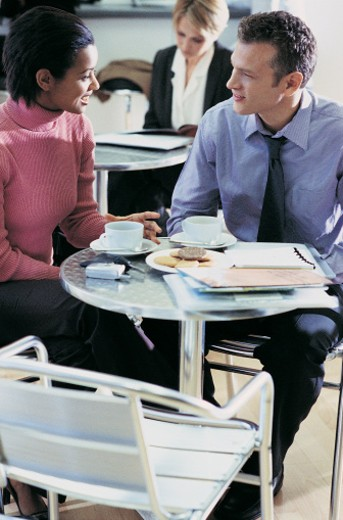 Two Business Colleagues Having a Discussion Around a Table on a Coffee Break : Stock Photo