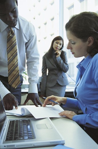 Businessman Showing a Businesswoman Sitting at Her Desk a Document : Stock Photo