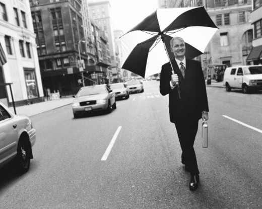 Stock Photo: 1527R-614007 Mature Businessman Walking in the Middle of a City Road With an Umbrella, Manhattan, New York, USA