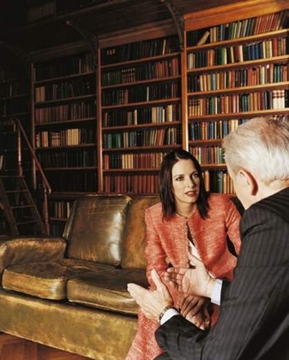 Stock Photo: 1527R-614021 CEO and a Businesswoman in Discussion Sitting on a Leather Sofa