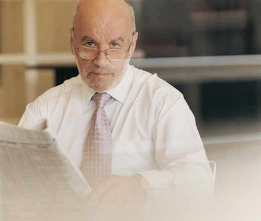 Portrait of a Mature CEO Wearing Spectacles and Holding a Newspaper : Stock Photo
