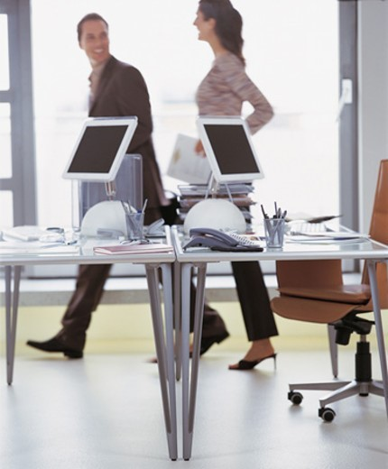 Stock Photo: 1527R-615010 Two Business Colleagues Walking Behind Desks in an Office