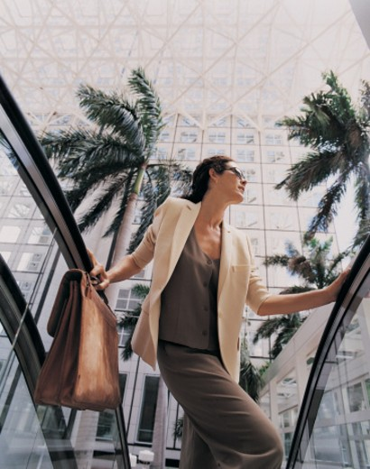 Low Angle View of a Businesswoman Wearing Sunglasses and Holding a Briefcase Ascending an Escalator : Stock Photo