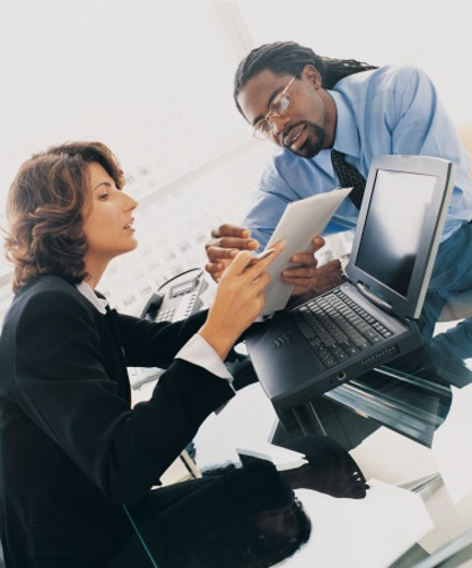 Two Business Colleagues Sitting at a Desk and Discussing a Document : Stock Photo
