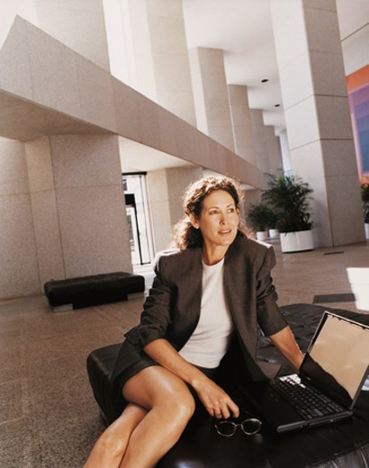 Stock Photo: 1527R-615048 Businesswoman Sitting on a Bench in an Office Lobby by Her Laptop