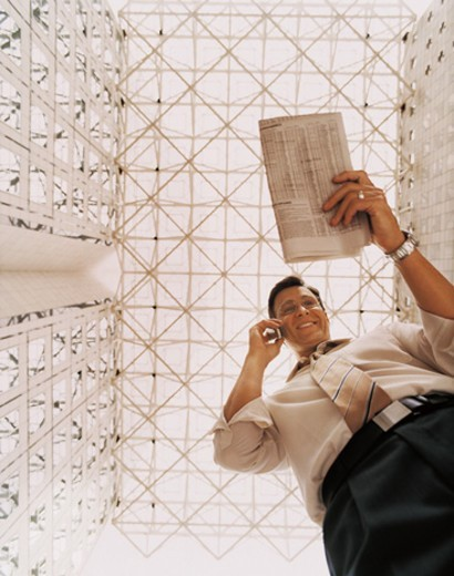 View From Below of a Businessman Reading a Newspaper and Using His Mobile Phone in an Office Lobby : Stock Photo