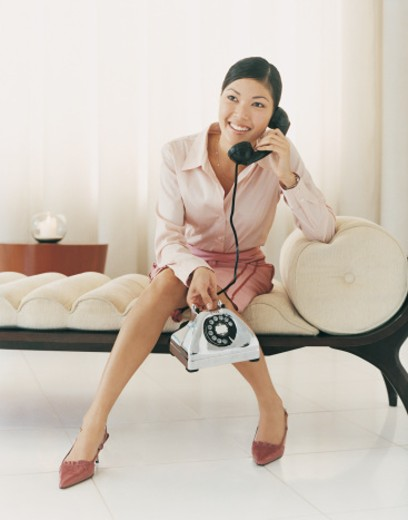 Stylish Businesswoman Sitting on a Chaise Lounge Using a Telephone : Stock Photo