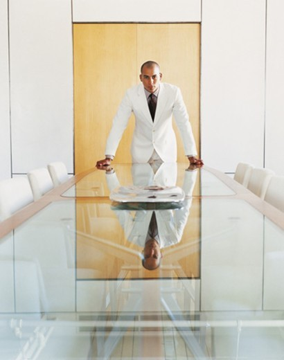Stock Photo: 1527R-643078 Portrait of a Confident Businessman Standing at the End of a Table in a Conference Room