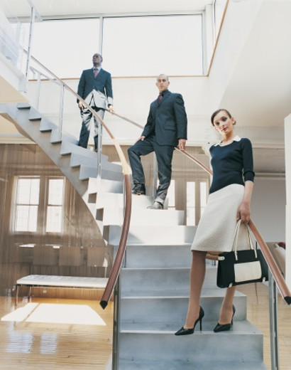 Portrait of Serious Stylish Businessmen and a Businesswoman Standing on a Modern Office Stairway : Stock Photo