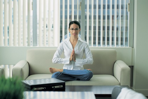 Stock Photo: 1527R-654009 Portrait of a Young Businesswoman Sitting in the Lotus Position on an Office Sofa With Her Hands Together