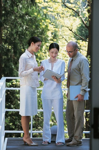 Three Business Colleagues Reading a Document Standing on a Balcony : Stock Photo