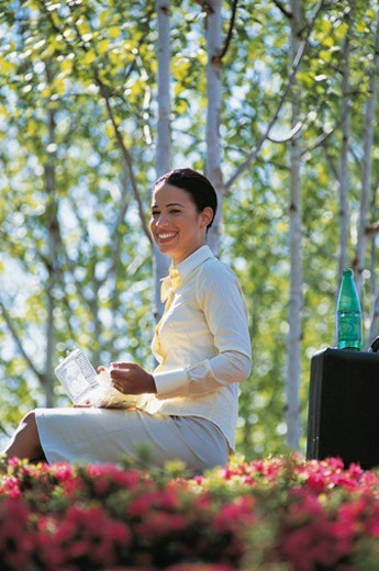 Portrait of a Young, Smiling Businesswoman Sitting in a Park With Her Packed Lunch : Stock Photo