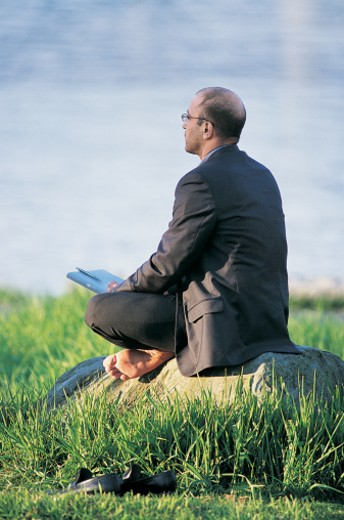 Thoughtful Businessman Sitting on Top of a Rock on Grass Holding a Folder and a Pen : Stock Photo