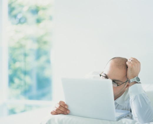 Stock Photo: 1527R-654080 Businessman Lying in Bed and Working on a Laptop