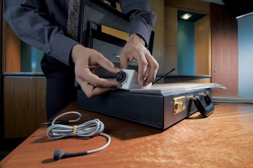 Businessman in An office Removing a Small Surveillance Camera From a Briefcase : Stock Photo