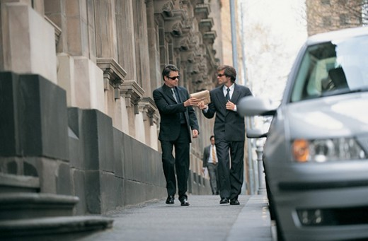 Suspicious Businessman Walking on a City Pavement Passing a Parcel to a Businessman Walking Next to Him : Stock Photo