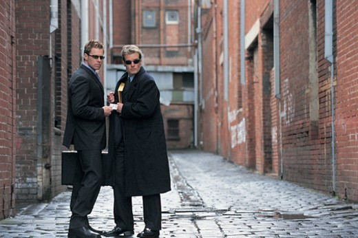 Suspicious Businessmen Standing in a Backstreet Giving and Receiving a Bundle of Money and An Envelope : Stock Photo