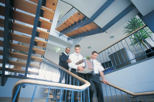 Security Guards Assisting a Suspicious Businessman Down a Flight of Stairs Carrying a Box : Stock Photo