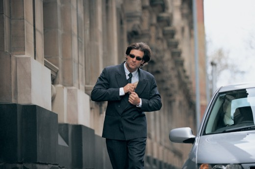 Businessman Walking in the City Hiding a Parcel in His Suit : Stock Photo