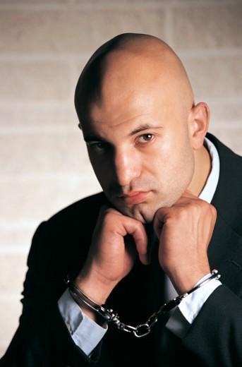Stock Photo: 1527R-658012 Portrait of a Criminal Businessman Wearing Handcuffs