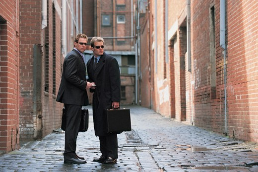 Stock Photo: 1527R-658014 Suspicious Businessmen Standing in a Backstreet Giving and Receiving a Bundle of Money