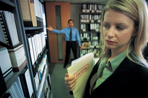 Stock Photo: 1527R-658016 Young Businesswoman Discovered By a Businessman Taking a Confidential File From Shelving in An Office