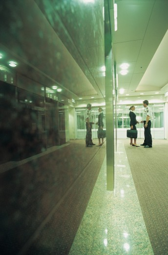 Stock Photo: 1527R-658017 Suspicious Businesswoman and Security Guard Standing in a Hotel Lobby