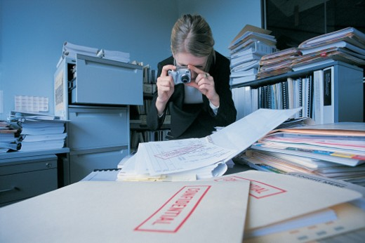 Businesswoman Taking Photographs of Confidential Documents in a Cluttered Office : Stock Photo