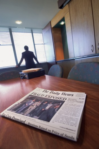 Stock Photo: 1527R-658019 Newspaper on a Table in a Conference Room Showing a Corporate Crime Headline and a Businessman Looking Through a Window