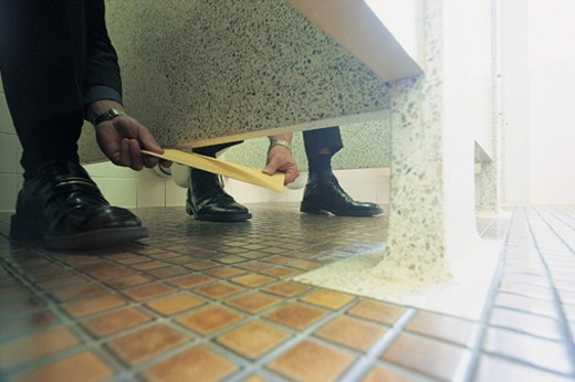 Stock Photo: 1527R-658023 Ground Level View of Businessmen Passing An Envelope in a Public Lavatory