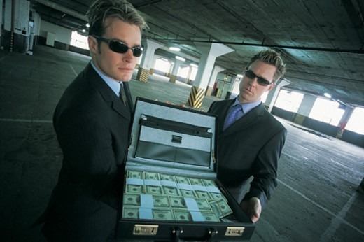 Stock Photo: 1527R-658025 Portrait of Criminal Businessmen Standing in a Car Park Showing An Open Briefcase Full of Bundles of Money
