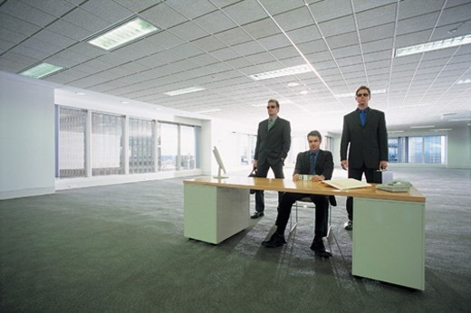 Portrait of a Criminal Businessman Sitting Behind a Desk Between to Bodyguards in An Empty Open Plan office Holding a Bundle of Banknotes : Stock Photo