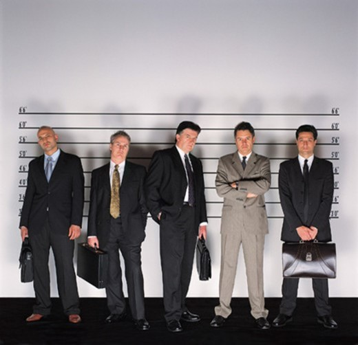 Group of Serious Businessmen Standing Holding Briefcases in a Police Line-up and a Man With His Arms Crossed : Stock Photo