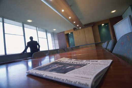 Newspaper on a Table in a Conference Room Showing a Corporate Crime Headline and a Businessman Looking Through a Window : Stock Photo
