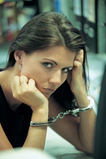 Stock Photo: 1527R-658031 Portrait of a Guilty Businesswoman Sitting at a Desk Wearing Handcuffs