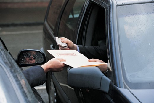 Criminal Businessman Sitting in a Car in a Car Park Buying a Confidential File With a Bundle of Money From Another Businessman Sitting in a Car : Stock Photo