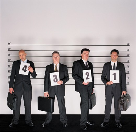 Group of Serious Businessmen Standing Holding Briefcases and Placards in a Police Line-up : Stock Photo