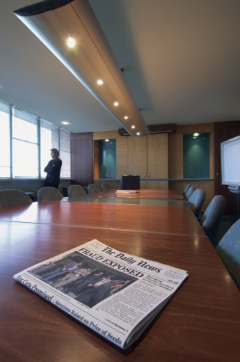 Newspaper on a Table in a Conference Room Showing a Corporate Crime Headline and a Pensive Businessman Looking Through a Window : Stock Photo