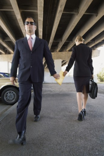 Stock Photo: 1527R-658040 Suspicious Businessman Passing An Envelope to a Businesswoman in a Car Park Below An Underpass