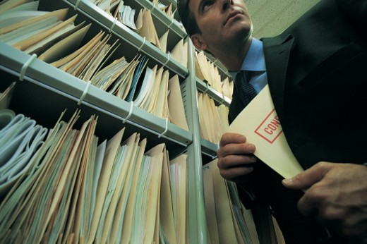 Stock Photo: 1527R-658044 Businessman Taking a Confidential File From a Filing Cabinet